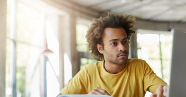 Stylish Afro American hipster male with bushy hairstyle wearing casual T-shirt being focused into screen of laptop sitting in spacious light room with big windows working with literature and internet